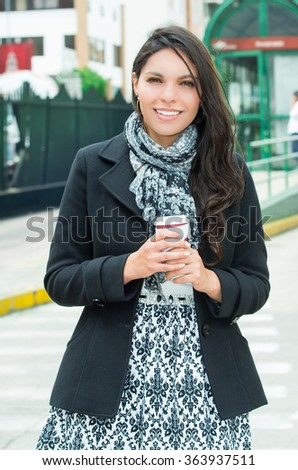 Classy woman wearing dark coat and black white clothing urban environment standing with back against brick wall smiling to camera - stock photo
