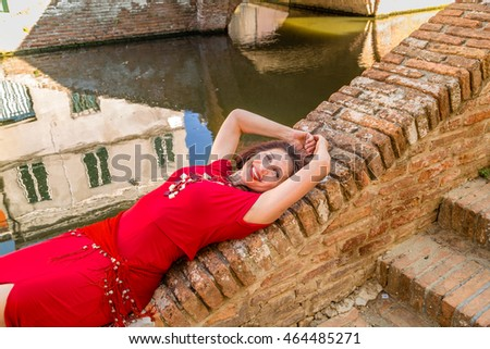 Classy woman with arms over head sitting on ancient bridge in Comacchio, a village you must visit in Italy, also called The Little Venice