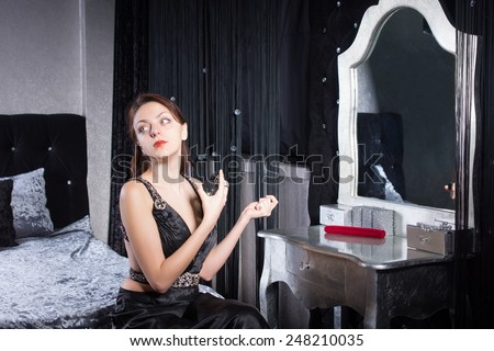 Classy Young Woman in Black Dress Spraying Perfume While Preparing for a Date. - stock photo
