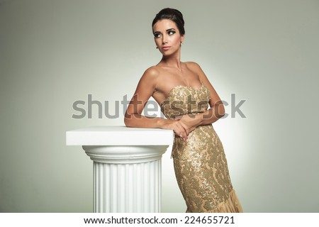 classy young woman in long elegant dress, standing near column and looks away in studio - stock photo