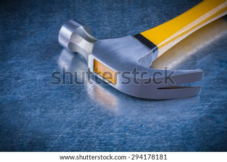 Claw hammer on scratched vintage metallic background construction concept. - stock photo