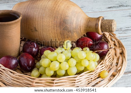 Clay bottle, a glass with wine, grapes and ripe plums in a wicker basket on a light wooden table.