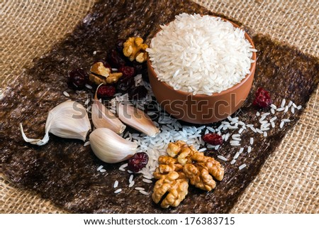 Clay bowl with rice, cranberries and garlic on a piece of nori - stock photo