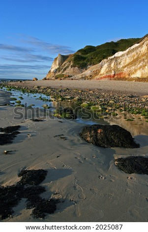 Clay cliffs on a seashore scattered with pebbles and a tidal pool. - stock photo