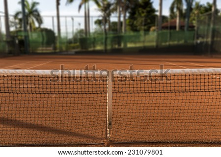 Clay (Dirt) Tennis Court, under the sunset. - stock photo