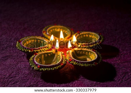 Clay diya lamps lit during Diwali Celebration. Greetings Card Design Indian Hindu Light Festival called Diwali - stock photo