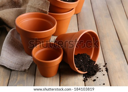 Clay flower pots and soil, on wooden table - stock photo