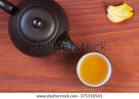 Clay glazed bowl with brewed tea and clay teapot on red wooden table decorated yellow rose petal, top view with place for text - stock photo