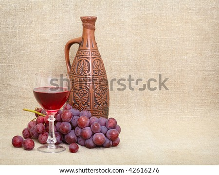 Clay jug with Georgian wine, a glass and grapes - a still-life - stock photo