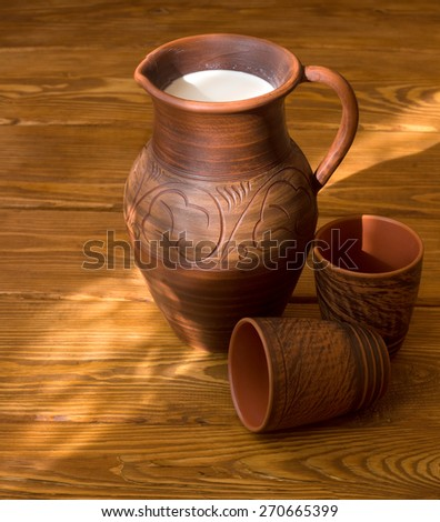Clay jug with milk on a wooden table - stock photo