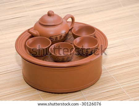 Clay little table for tea with cups and teapot - stock photo