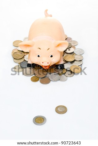 Clay piggy bank on a pile of coins - stock photo