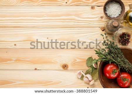 clay plate with tomatoes, herbs, thyme, rosemary, sea salt, olive oil in clay jug, garlic,  pepper, bay leaf on wooden background, top view - stock photo
