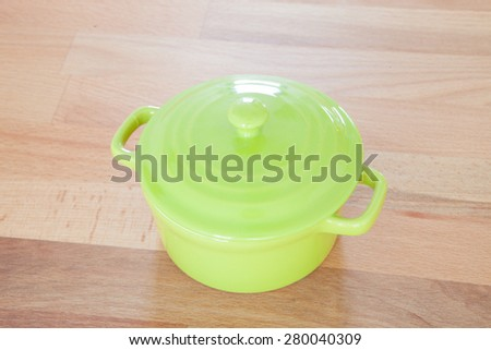 Clay pot in green on a wooden board - stock photo