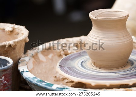 Clay pot on a pottery wheel in outdoor workshop - stock photo