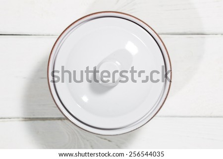 Clay pot on a white wooden table - stock photo