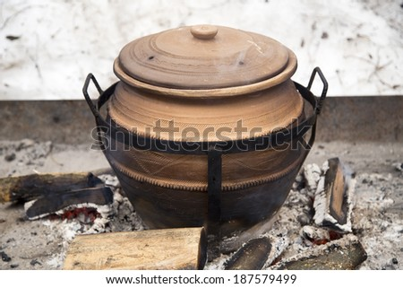 Clay pot on fire - stock photo