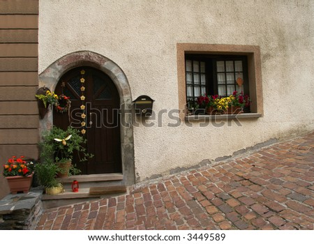 clay pots and other decorations adorn a home on a cobblestoned street