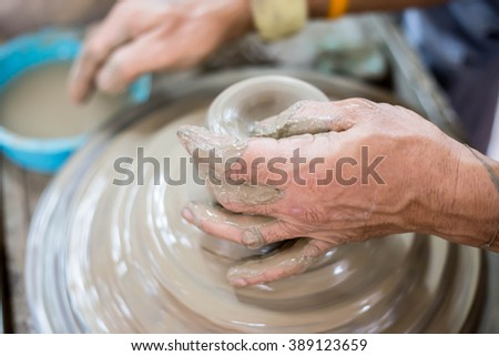 Clay potter creating on the pottery wheel 2 - stock photo