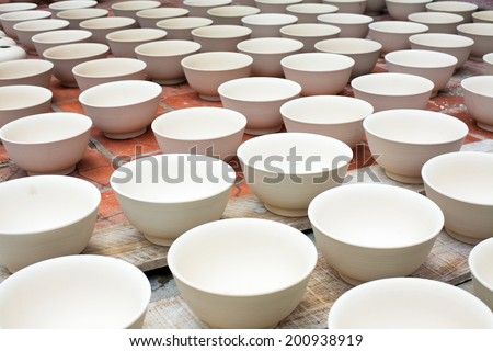 "Clay pottery are dried in the road. Bat Trang village-  ""the village of bowls"". This is the oldest and best known pottery village of Hanoi, Vietnam. - stock photo"