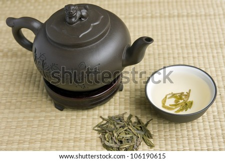Clay teapot and a cup of green tea on a bamboo mat - stock photo