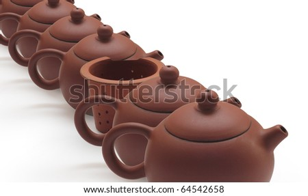 Clay teapots and tea strainer at row  on white background