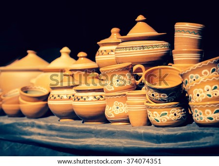 Clay utensil - pottery on the counter of the rural fairs in Ukraine. Crockery shop - pottery utensils in retro style. Handmade utensils in folk style and old traditions. - stock photo