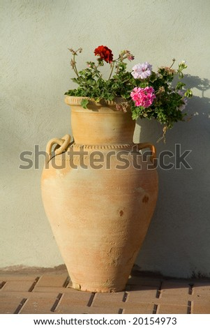 Clay vase with a blossoming geranium - stock photo