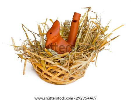Clay whistle bird in a straw nest