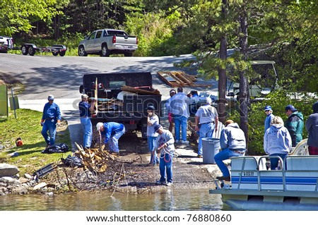 CLAYTON, GA - MAY 6: A group of volunteers clean tornado debris on May 6, 2011 in Rabun County, Lake Burton, Clayton, GA. It was hit with the worst tornado to ever hit the area. - stock photo