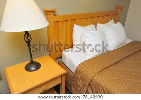 Clean and cozy bed with lamp on side table. - stock photo