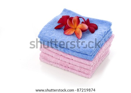 Clean and fresh towel with red frangipani flowes at the top isolated white background