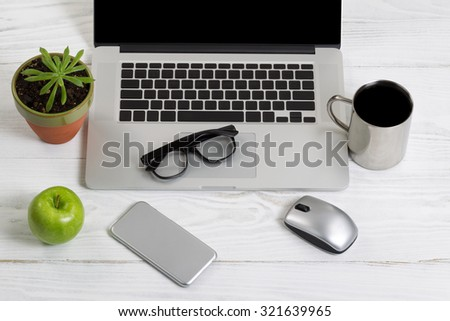 Clean and organized white desktop with office work objects and snacks. Layout in horizontal format. - stock photo