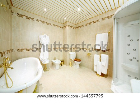 Clean bathroom with bath, shower cabin, toilet and bidet in classic style. - stock photo