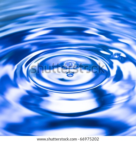 Clean blue drop of water splashing in clear water. Abstract blue background