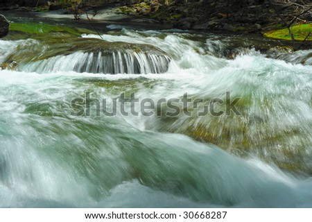 Clean clear water racing down the river bed over rocks and boulders creating rapids and small waterfall - stock photo