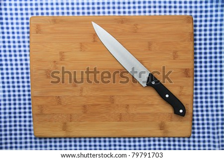 Clean Cutting Board and Knife isolated on blue and white checkered background - stock photo