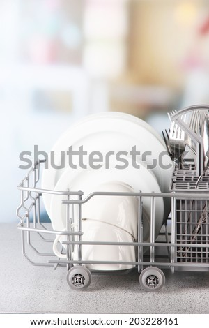 Clean dishes drying on metal dish rack on light background - stock photo