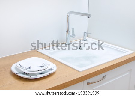 Clean dishes near the sink in the kitchen. - stock photo