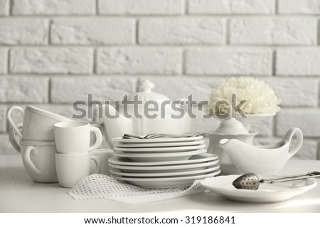 Clean dishes on table on brick wall background - stock photo
