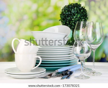 Clean dishes on table on natural background - stock photo