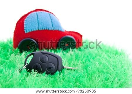 Clean ecology concept car and key for it on green grass. Focus on the key. Isolated on white. - stock photo