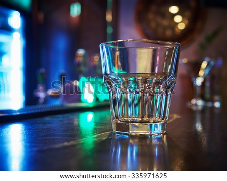 clean empty old fashion rocks tumbler whiskey glass on a dark bar counter with a background of neon lights and bokeh - stock photo