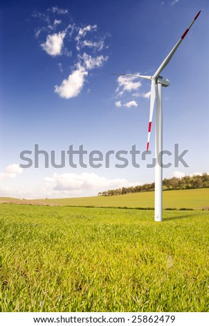 Clean energy concept with green grass and wind turbine