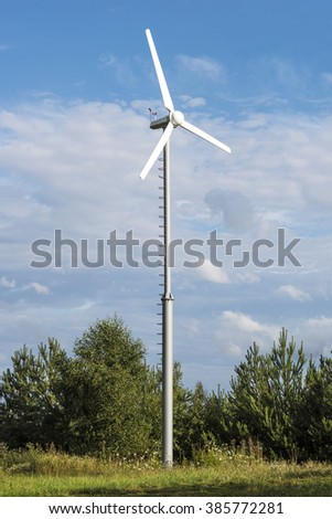 Clean energy white wind turbine in green field with flowers and small trees.