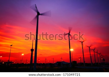 Clean energy wind turbine silhouettes are working at twilight.