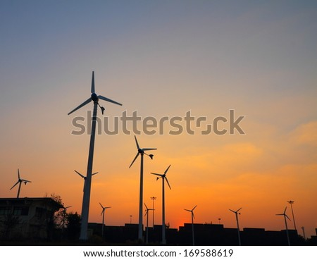 Clean energy wind turbine silhouettes at sunset, at Chonburi Thailand
