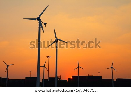 Clean energy wind turbine silhouettes at sunset, at Thailand - stock photo