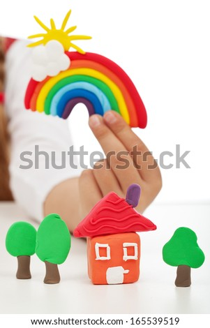 Clean environment concept - child hand holding colorful figures made of clay - stock photo