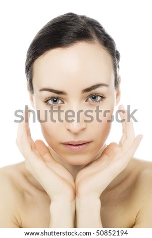 clean face of a young woman looking into camera - stock photo
